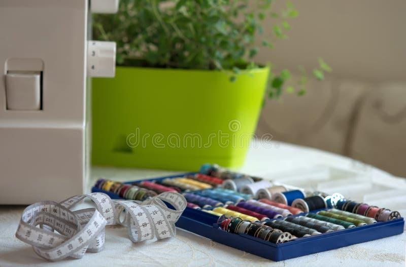 Herramientas de costura en la tabla - un sistema de hilos multicolores en las bobinas, las costureras de la ruleta y la pieza de  imagenes de archivo