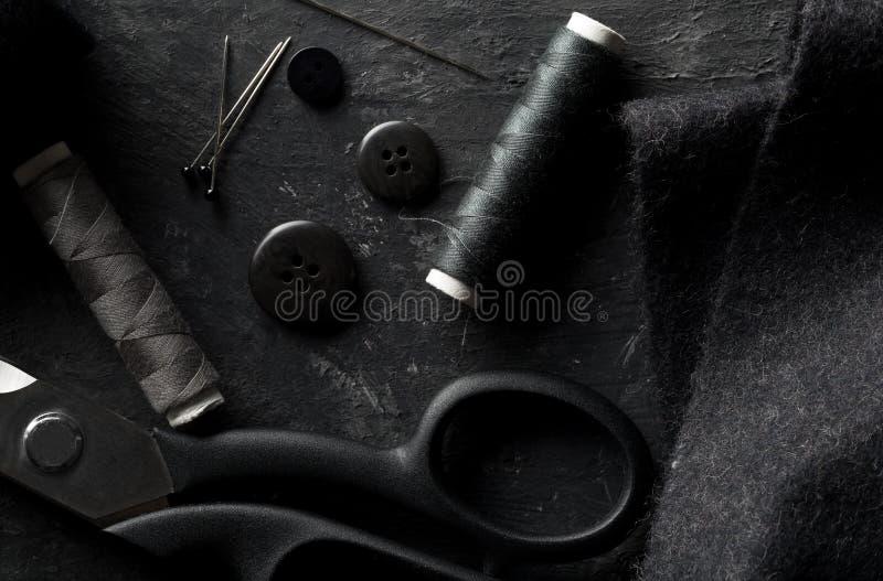 Herramientas de costura puestas planas de la visión superior con los botones, la tela de materia textil, el hilo, las agujas y la fotografía de archivo