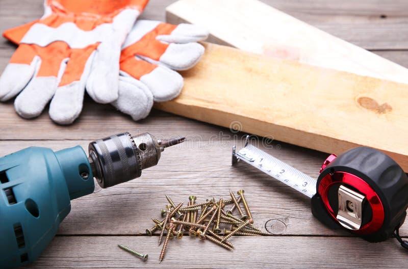 Herramientas de la construcción en un escritorio de madera gris imagen de archivo