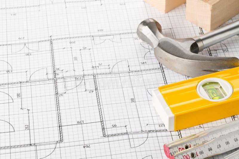 Herramientas de la construcción y tiras de madera en plan arquitectónico de la construcción de viviendas del modelo con el espaci fotos de archivo libres de regalías