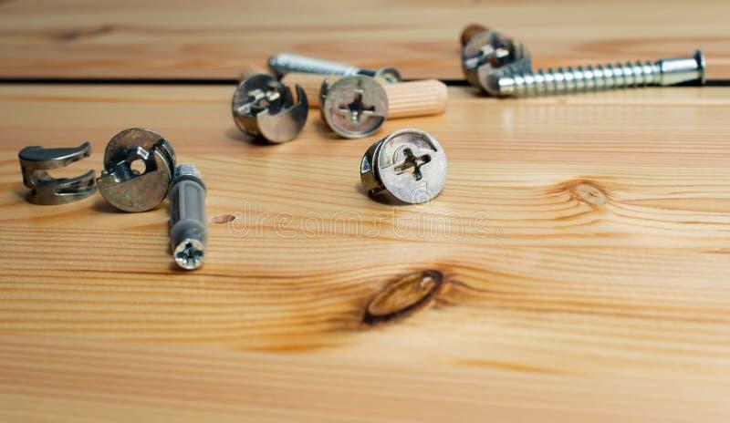 Herramientas de la construcci?n Los tornillos, nueces - y - pernos en fondo de madera Concepto de las mejoras para el hogar de la imagenes de archivo
