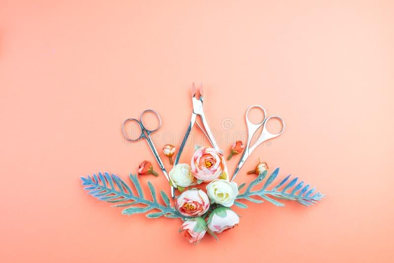 Herramientas de la manicura en un fondo rosado adornado con las flores foto de archivo