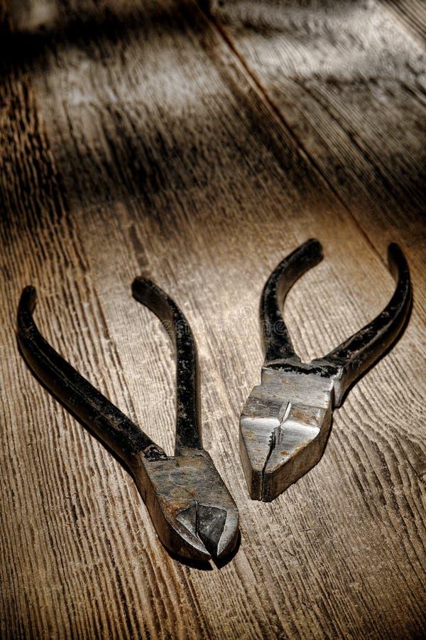 Herramientas de los alicates del metal de la vendimia en la madera antigua de Grunge fotos de archivo libres de regalías