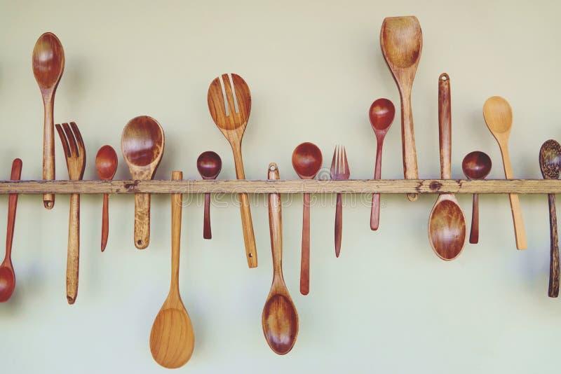 Herramientas de madera de la cocina: la cuchara de madera, bifurcación de madera, espátula de madera, cuelga en la pared blanca fotografía de archivo libre de regalías