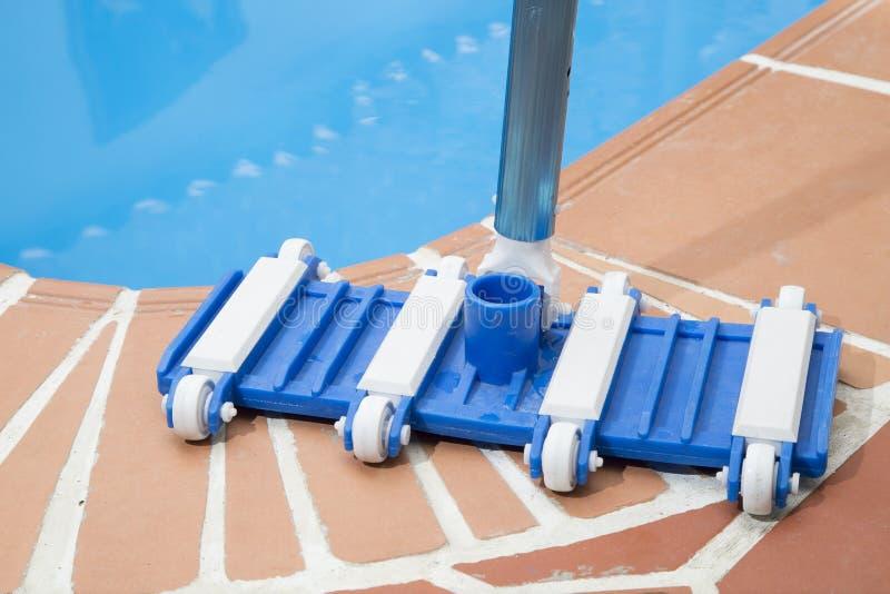 Herramientas de mantenimiento de la desnatadora del cepillo y de la hoja de la pared en cubierta al lado de la piscina fotografía de archivo libre de regalías