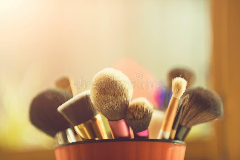 Herramientas del artista de maquillaje cepillo del maquillaje para el cosmético de moda en taza rosada imagen de archivo libre de regalías