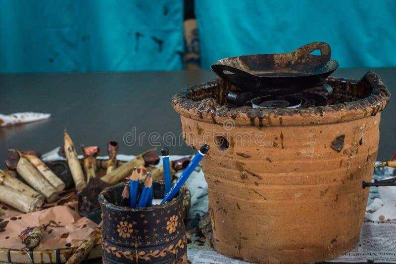Herramientas del batik, biselaje y cera caliente encima de la tabla de madera para el batik que procesa con la pared azul como fo fotos de archivo
