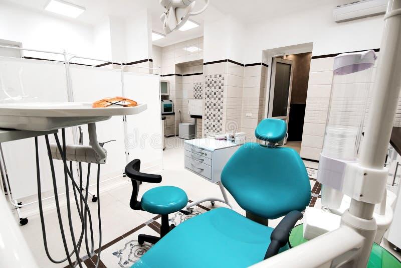 Herramientas del dentista y el esperar profesional de la silla de la odontología fotos de archivo