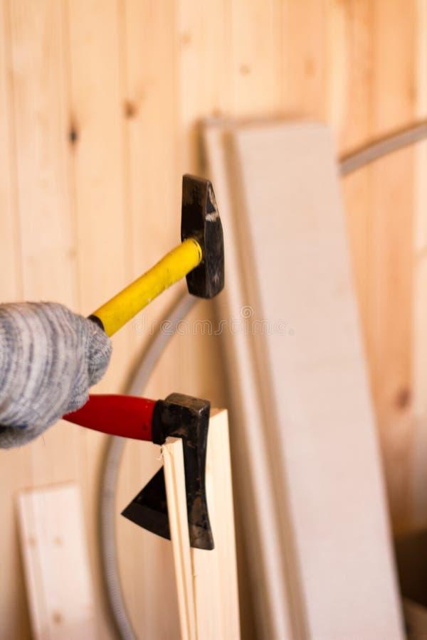 Herramientas del edificio woodwork Martillo y hacha en las manos masculinas foto de archivo libre de regalías