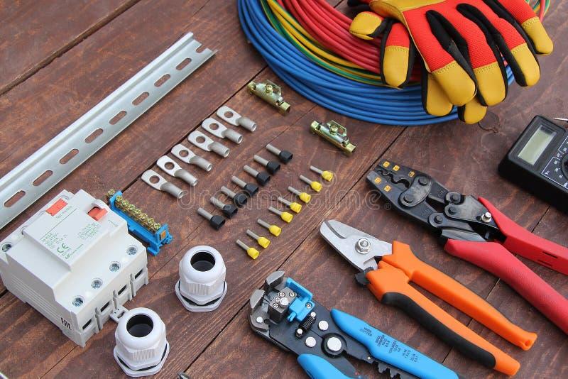 Herramientas del electricista con el alambre rojo y azul presentado en una superficie de madera del color oscuro imagenes de archivo