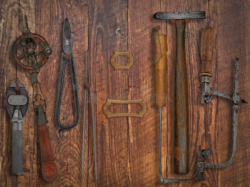Herramientas del joyero del vintage sobre la pared de madera fotografía de archivo