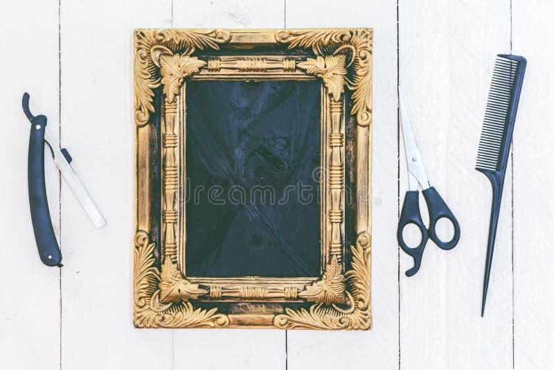 Herramientas del marco y del peluquero del vintage en fondo de madera foto de archivo libre de regalías