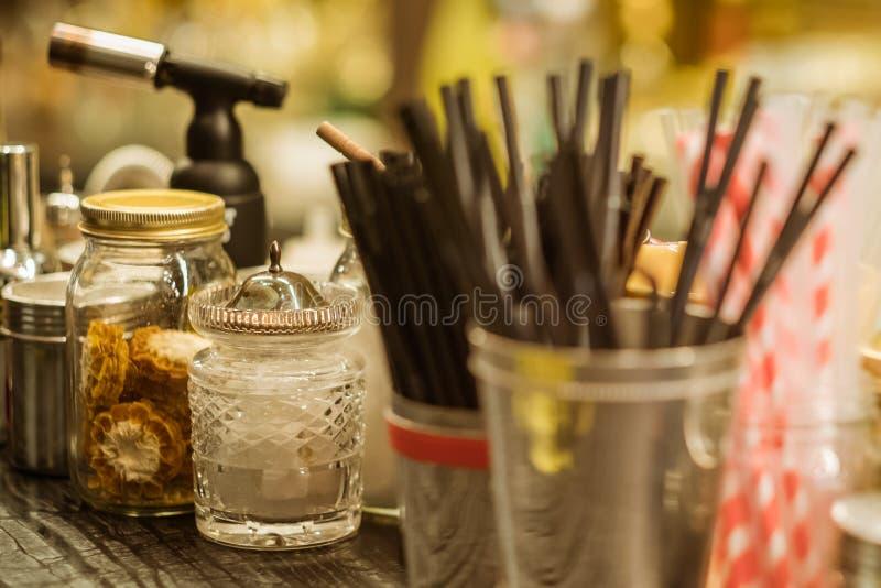 Herramientas e ingredientes profesionales del cóctel en las botellas de cristal y los tarros para los cócteles de moda modernos c foto de archivo