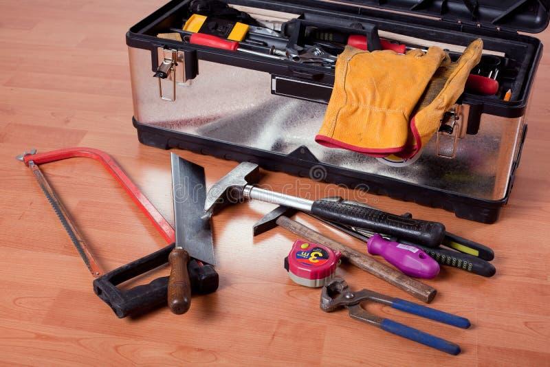 Herramientas en caja de herramientas en suelo de madera imagenes de archivo