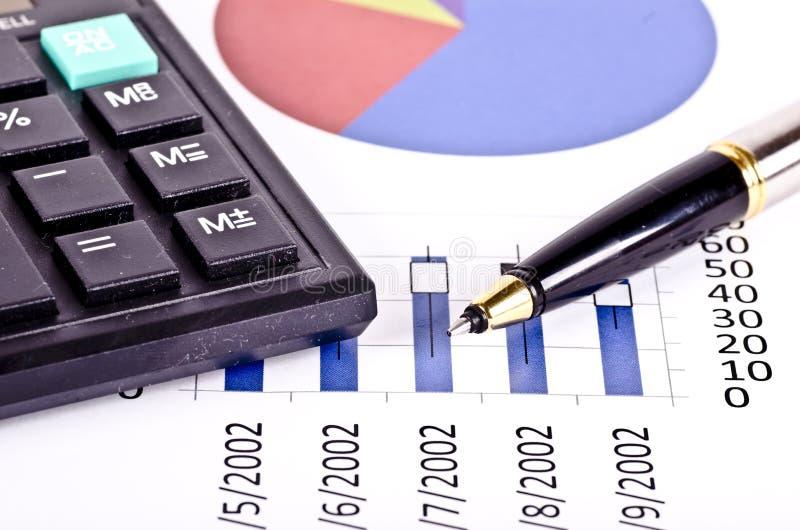 Herramientas financieras, calculadora, pluma sobre un informe foto de archivo