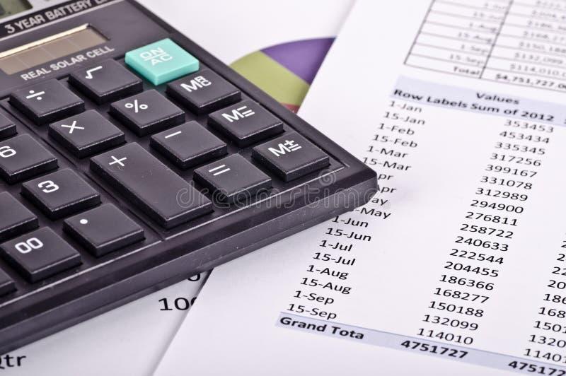 Herramientas financieras, calculadora sobre un informe financiero fotos de archivo libres de regalías