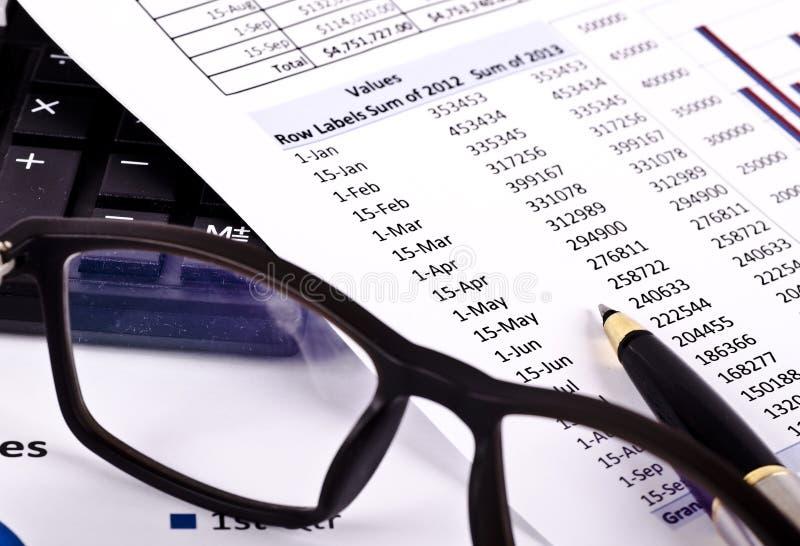 Herramientas financieras, pluma que señala sobre un informe y gafas foto de archivo libre de regalías