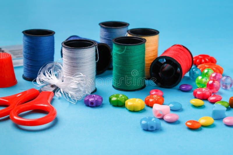Herramientas, gotas de la variedad y carretes de costura del hilo en superficie azul fotografía de archivo