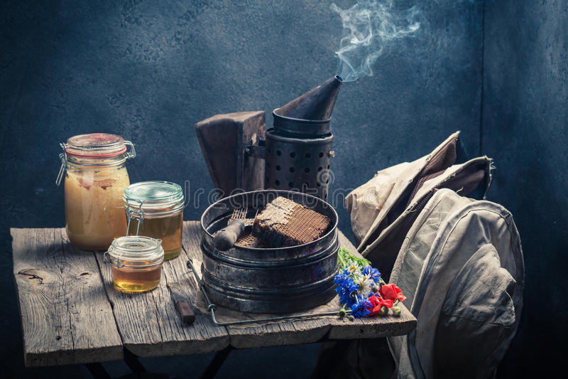 Herramientas oxidadas del apicultor con los panales, los sombreros y la miel imagen de archivo libre de regalías