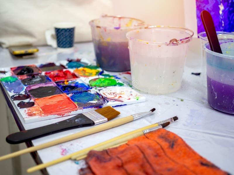 Herramientas para artistas, pinceles para pintar, balde blanco de agua y paleta de artistas de color acrílico en estudio de arte fotos de archivo libres de regalías