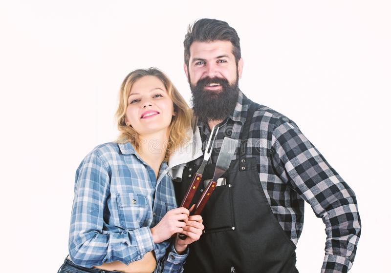Herramientas para asar la carne al aire libre Comida campestre y barbacoa Concepto culinario Inconformista barbudo y muchacha del fotos de archivo