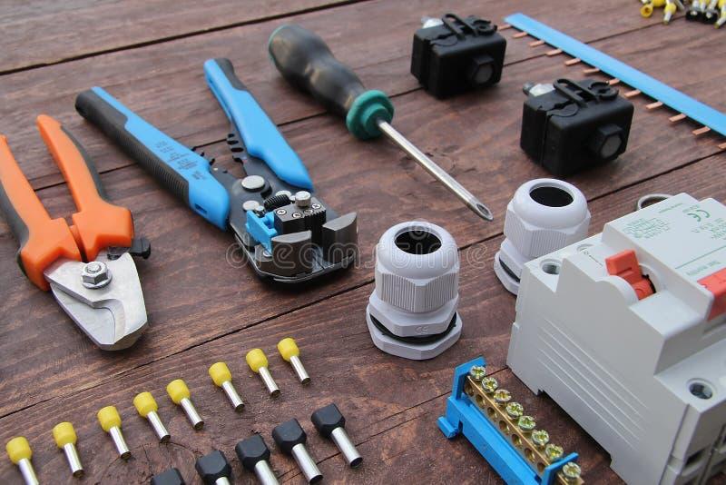 Herramientas para el trabajo eléctrico presentado en una superficie de madera del marrón imágenes de archivo libres de regalías
