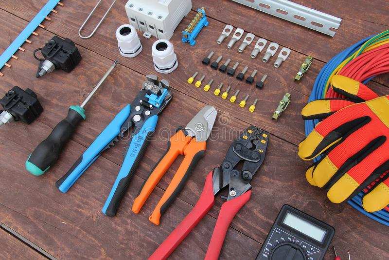 Herramientas para el trabajo eléctrico presentado en una superficie de madera del marrón imagen de archivo