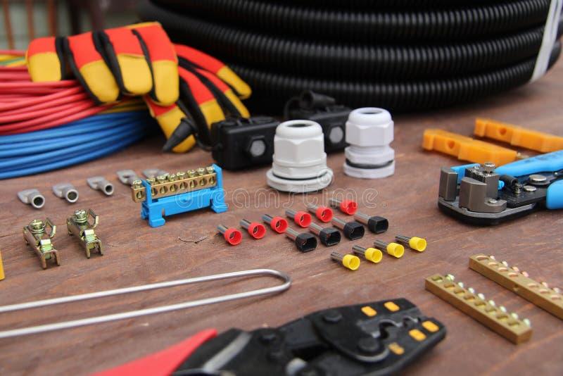 Herramientas para el trabajo eléctrico presentado en una superficie de madera del marrón imagen de archivo libre de regalías
