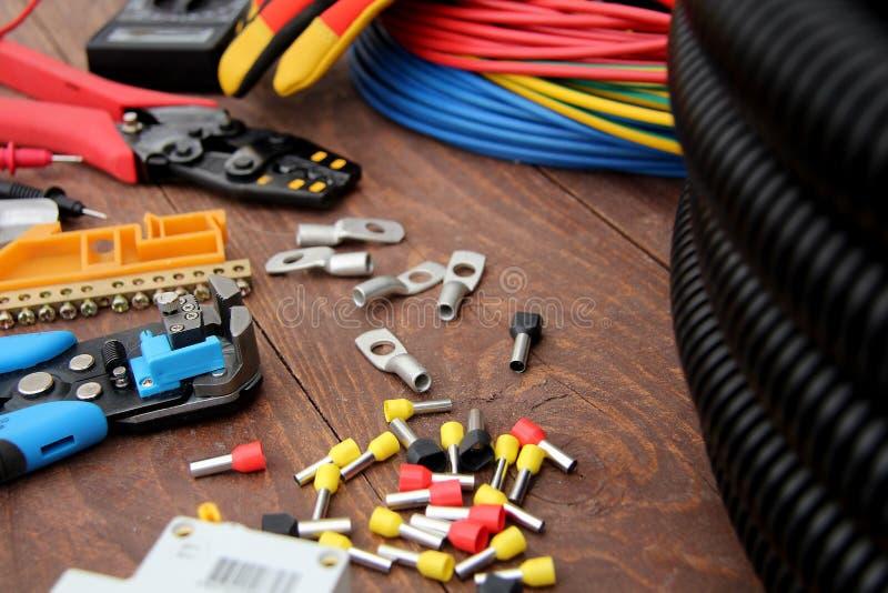 Herramientas para el trabajo eléctrico presentado en una superficie de madera del marrón fotografía de archivo libre de regalías