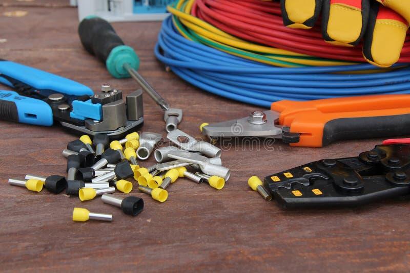 Herramientas para el trabajo eléctrico presentado en una superficie de madera del marrón foto de archivo