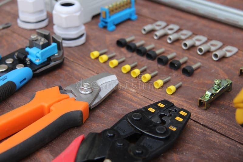 Herramientas para el trabajo eléctrico presentado en una superficie de madera del marrón fotografía de archivo