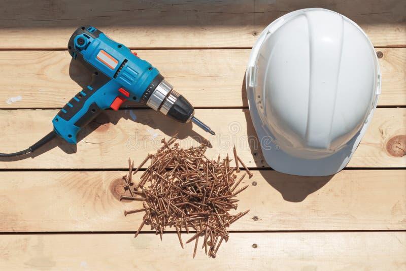 Herramientas para la construcción de un piso o de una terraza de madera Destornillador, tornillos penetrantes y casco en el piso  fotos de archivo