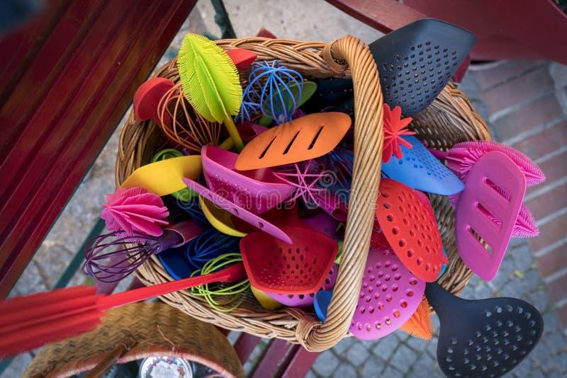 Herramientas plásticas coloridas de la cocina en una cesta foto de archivo