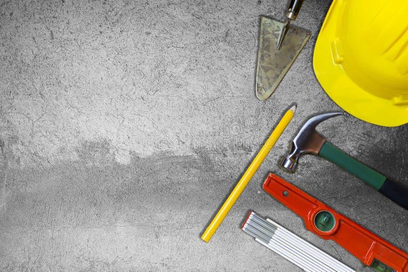 Herramientas protectoras del casco y del albañil en el muro de cemento de la pizca del fondo imagen de archivo