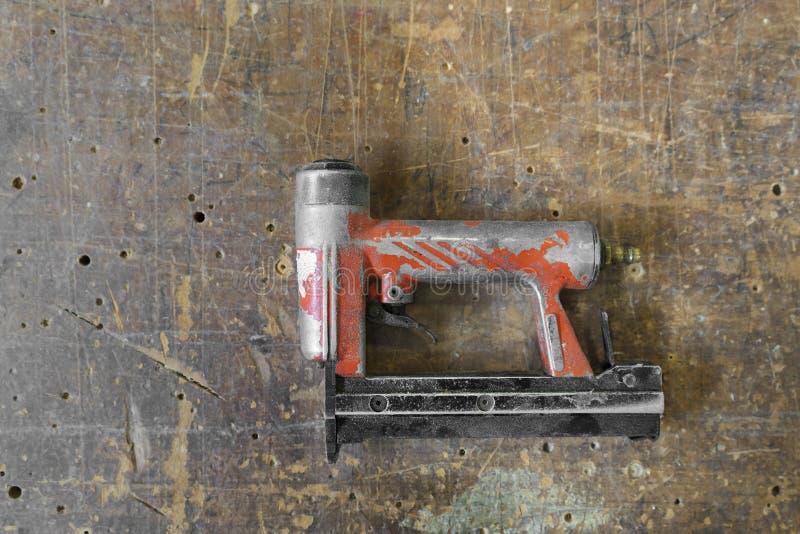 Herramientas rojas usadas viejas del carpintero del fabricante de clavos del aire o del arma del clavo imagen de archivo