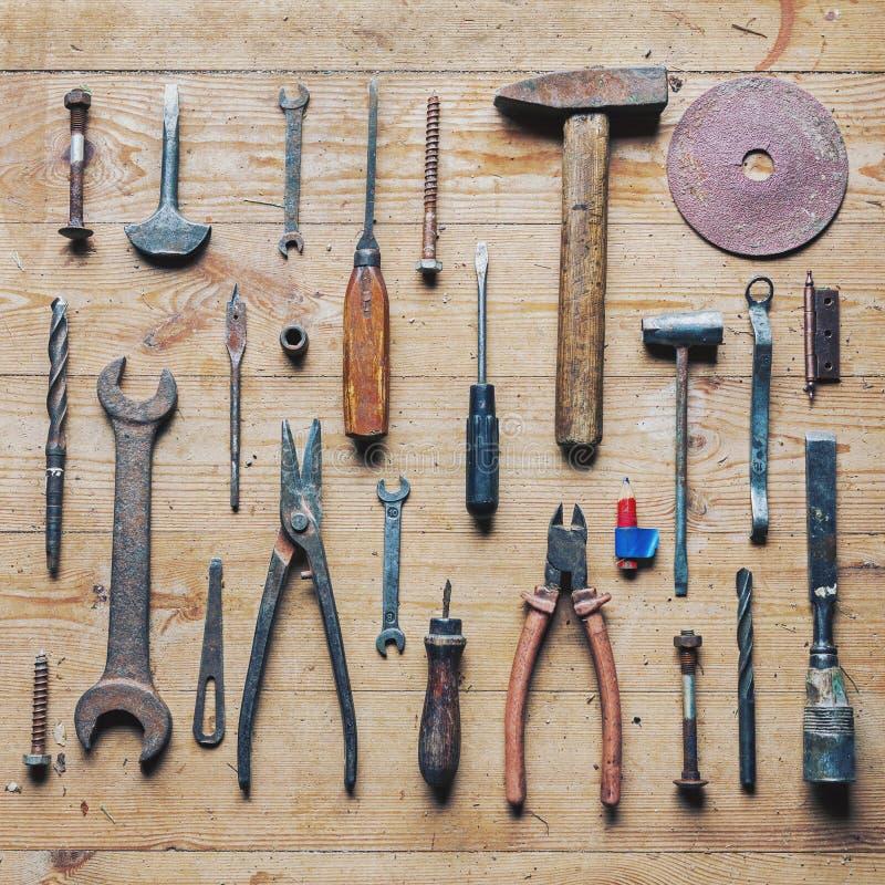 Herramientas sucias viejas de la reparación del vintage en fondo de madera foto de archivo libre de regalías