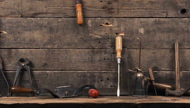 Herramientas usadas viejas del carpintero en la madera foto de archivo