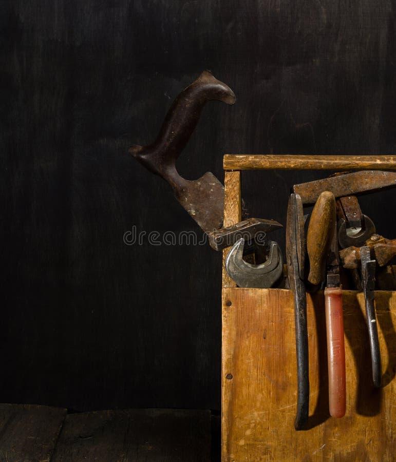 Herramientas usadas viejas en la caja de herramientas Fondo oscuro Iluminación del punto Rectángulo de madera aislado imagenes de archivo