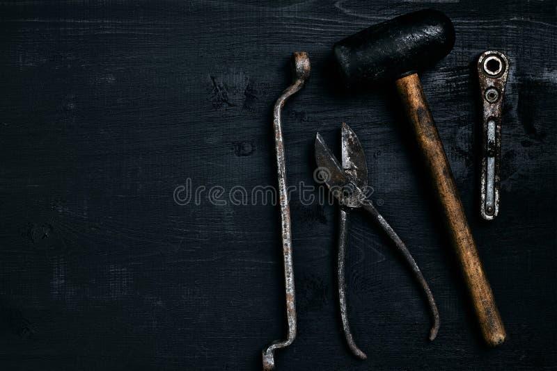 Herramientas viejas, oxidadas que mienten en una tabla de madera negra El martillo, cincel, metal scissors, llave foto de archivo libre de regalías