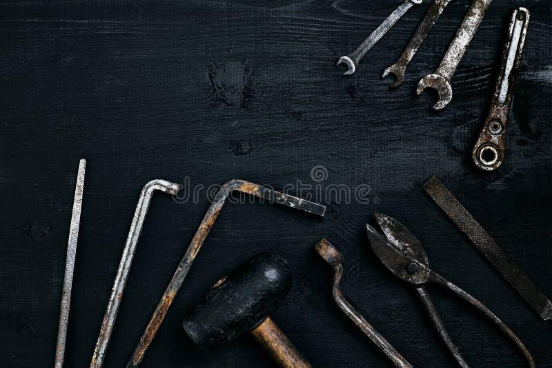 Herramientas viejas, oxidadas que mienten en una tabla de madera negra El martillo, cincel, metal scissors, llave fotos de archivo