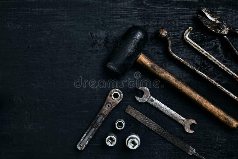Herramientas viejas, oxidadas que mienten en una tabla de madera negra El martillo, cincel, metal scissors, llave fotografía de archivo libre de regalías