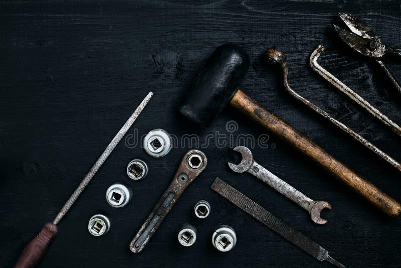 Herramientas viejas, oxidadas que mienten en una tabla de madera negra El martillo, cincel, metal scissors, llave imagen de archivo