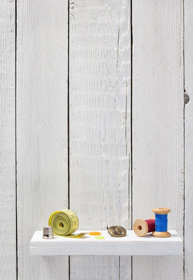 Herramientas y accesorios de costura en estante de madera foto de archivo libre de regalías