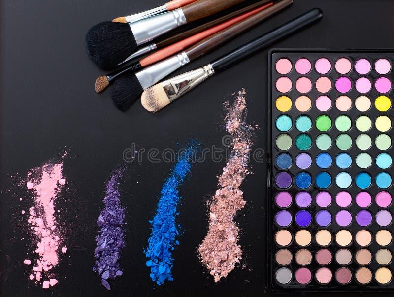 Herramientas y accesorios del maquillaje aislados en fondo negro Visión superior y mofa para arriba El lápiz labial, sombras de o foto de archivo libre de regalías