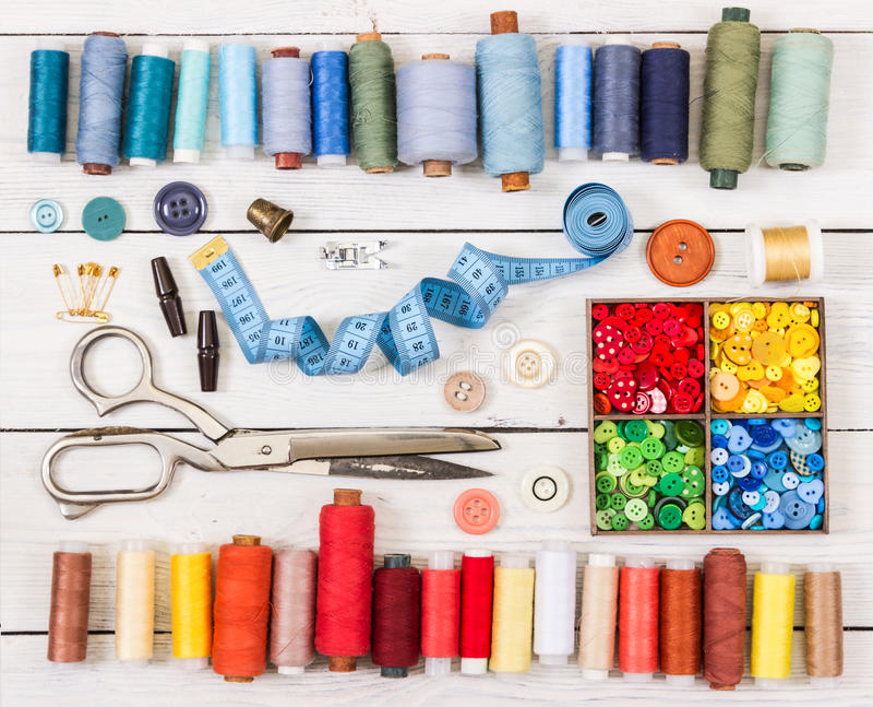 Herramientas y accesorios para coser en fondo de madera ligero imagenes de archivo