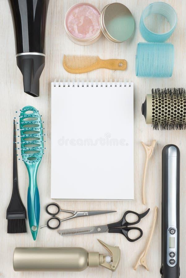Herramientas y accesorios profesionales de la peluquería con el cuaderno en blanco en el centro fotografía de archivo libre de regalías