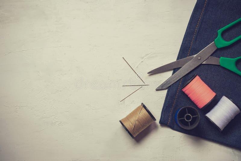 Herramientas y equipo de costura en el piso de madera blanco fotografía de archivo