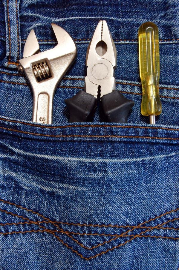 Herramientas y pantalones vaqueros imagenes de archivo
