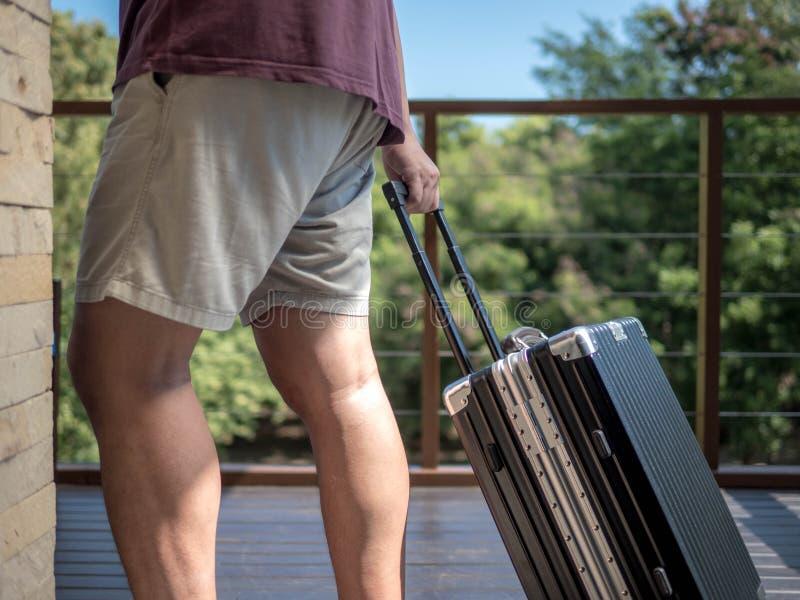 Herrenbekleidungskurze hosen, die ihr Gepäck zur Anpassung schleppen, um am Feiertag zu reisen stockfotografie