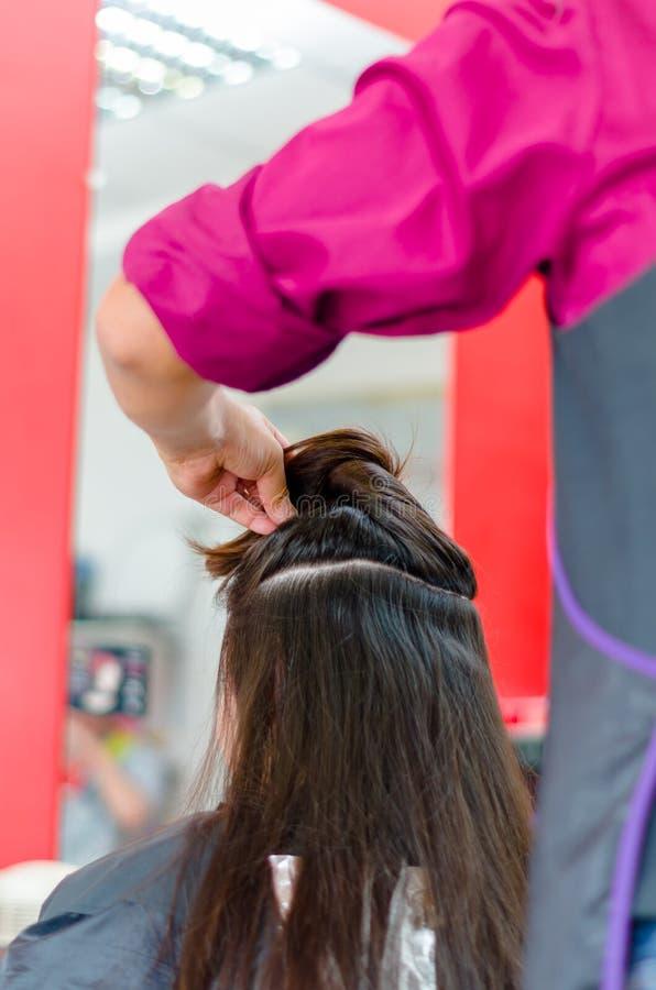Herrenfriseur, der alles vorbereitet, um ein langes braunes Haar zu schneiden lizenzfreies stockfoto